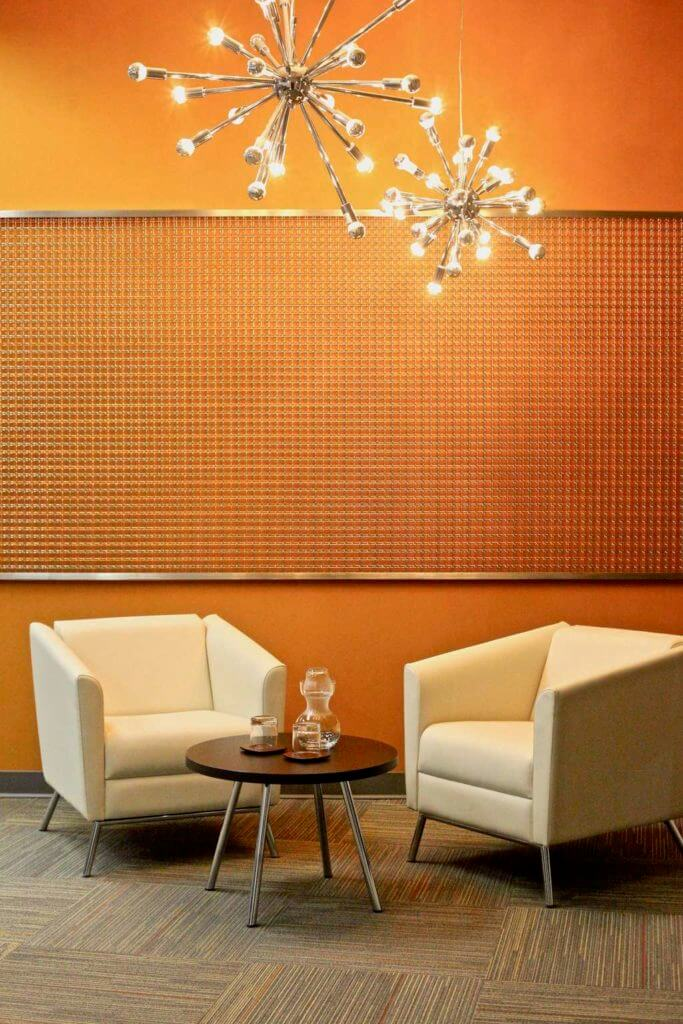Modern waiting area with silver wall decor, decorative silver chandelier and beige carpet tiles with orange accent color.