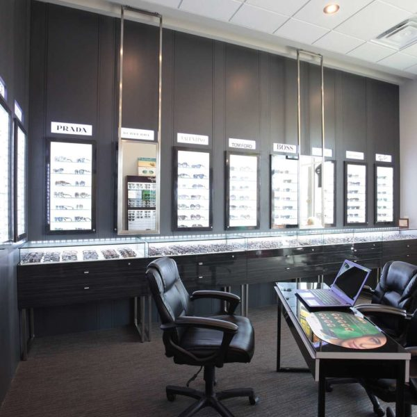 Optical store with with dark cabinets, suspended mirrors and leather chairs.