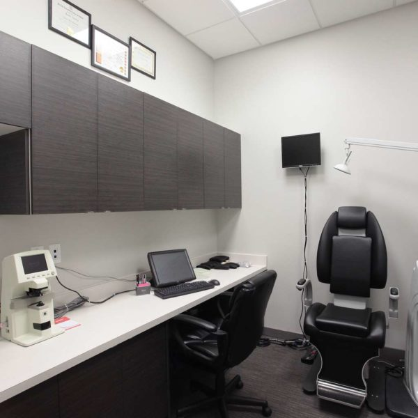 Optical treatment room with built-in dark cabinetry, white counters and medical equipment.