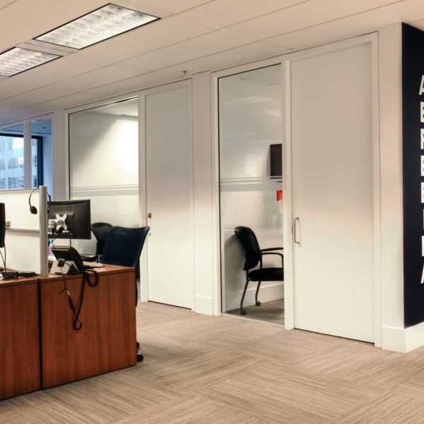Modern corporate office with open work area , executive glazed offices and graphic feature wall.