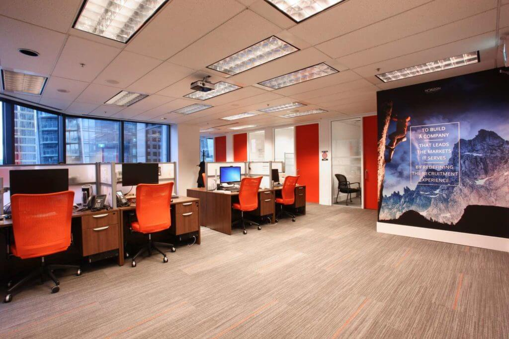 Open work area in the modern corporate office with the orange accents and the motivational wall print.