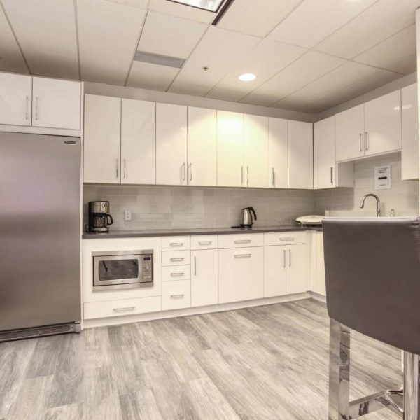 Large modern office kitchen with white cabinets, grey counters and bar sitting.