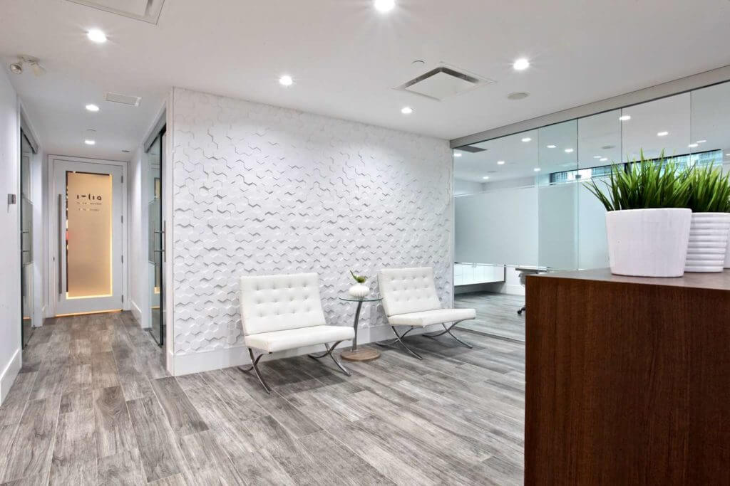 Reception area in a corporate downtown office with textured hexagonal wall panels and white leather barcelona chairs.