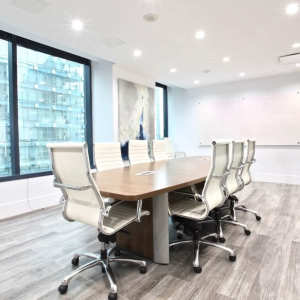 Modern corporate office boardroom with wood table and white chairs.