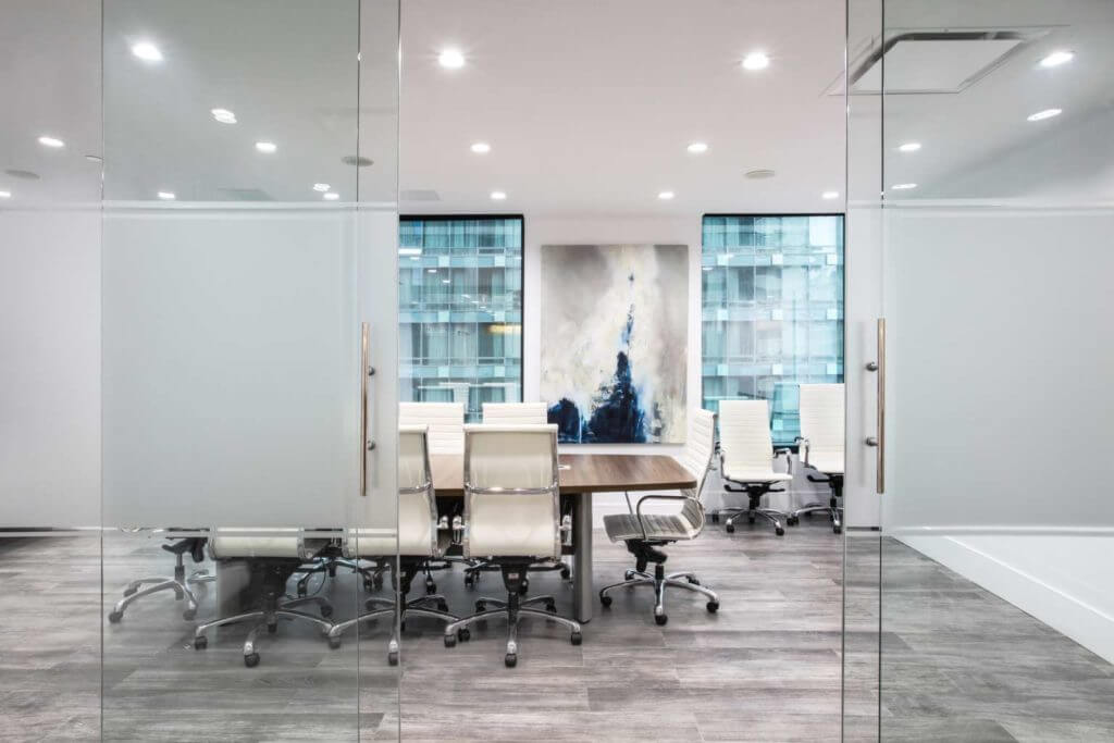 Modern boardroom with sliding glass doors and white chairs.