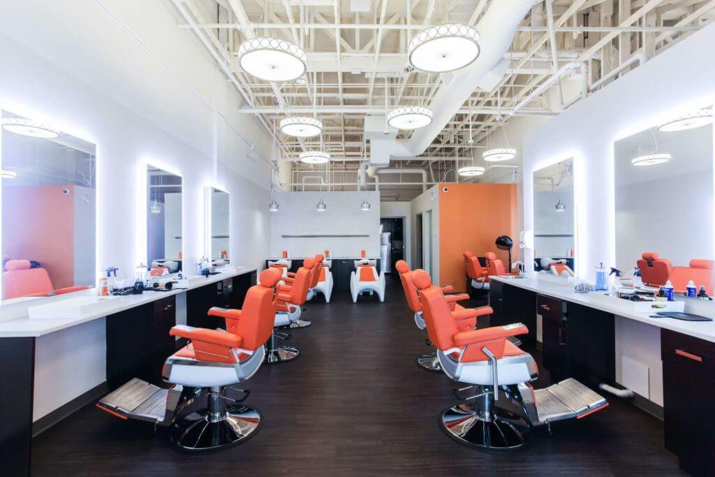 Interior of the chic beauty saloon with open ceiling, dark vinyl plank floor and orange saloon chairs.