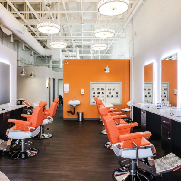 Interior of chic beauty saloon with dark vinyl plank floor, open ceiling and orange leather saloon chairs.