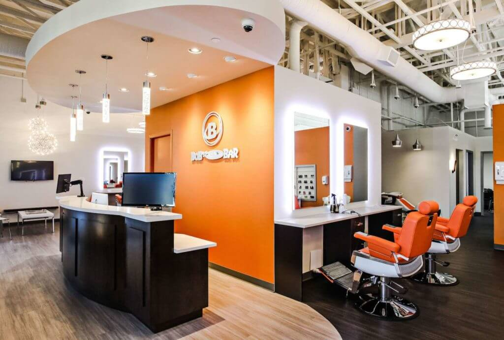 Modern reception desk with company logo, custom reception desk and LED mirrors on the orange accent wall.