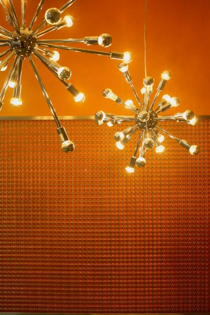 Orange accent wall with decorative cooper panels and the futuristic chandelier.