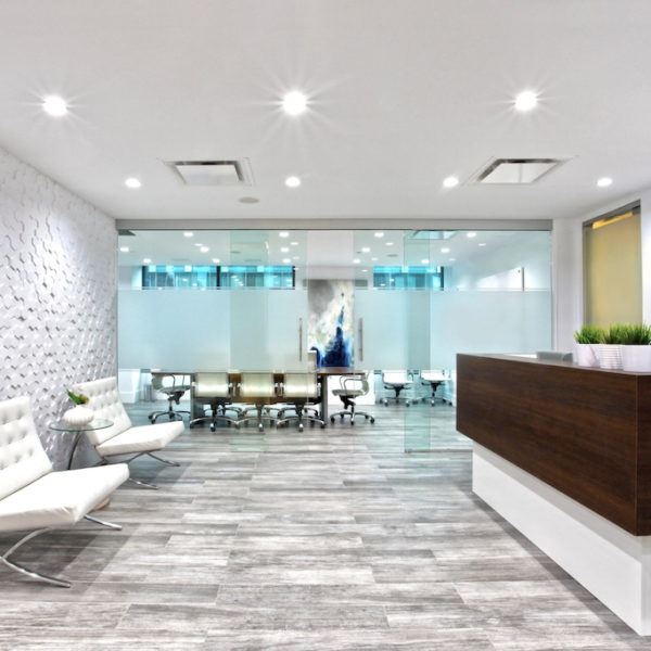 Modern reception area with textured feature wall and built-in reception desk.